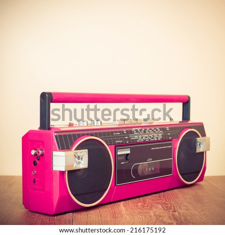 Retro pink radio cassette stereo tape recorder on table - stock photo