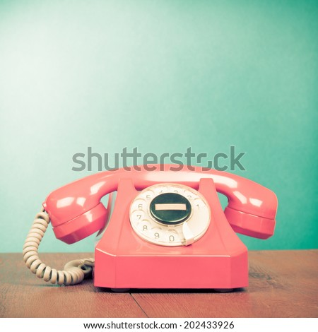 Retro pink telephone on wood table front mint green gradient background - stock photo