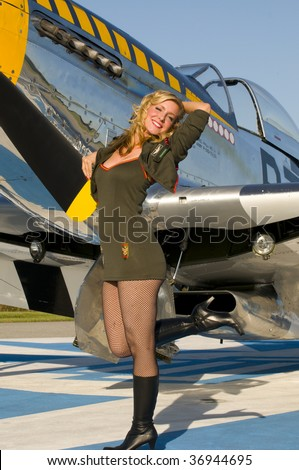 retro pinup girl in army uniform standing next to a world war two aircraft and smiling - stock photo