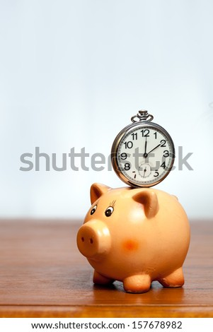 Retro pocket watch on a piggy bank