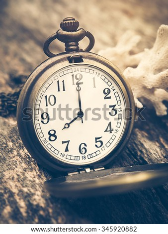 Retro pocket watch with antique number is showing 8 o'clock with white coral  out of focus background and on wooden background. Vintage style and filtered process. - stock photo