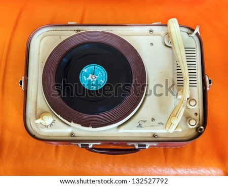 Retro portable turntable on orange background - stock photo
