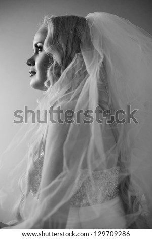 Retro portrait of a beautiful blonde bride posing over grey background. Daylight. Hollywood style. Black and white (monochrome) studio shot - stock photo