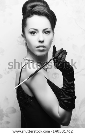 Retro portrait of a beautiful woman in great cocktail dress smoking a cigarette with holder. Jewelry and Beauty. Vintage (Hollywood) style. Classic old movie star. Black and white studio shot - stock photo