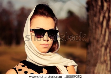 Retro portrait of beautiful young girl in glasses and a white scarf - stock photo