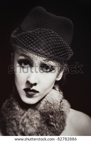 Retro portrait of beautiful young woman in hat with veil