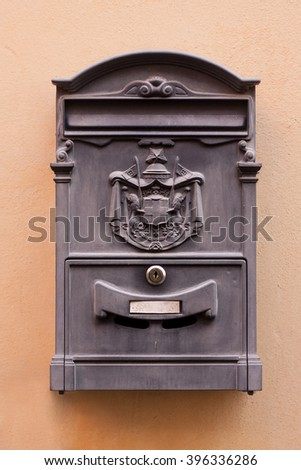 Retro postbox mounted on wall with white board for text - stock photo