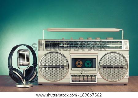 Retro radio and cassette player, microphone, headphones on table - stock photo