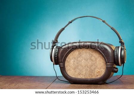 Retro radio and headphones on blue background - stock photo