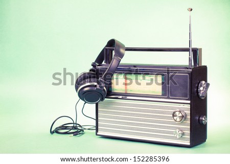 Retro radio and headphones on mint green background - stock photo