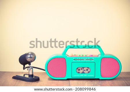 Retro radio cassette recorder, old microphone on table - stock photo