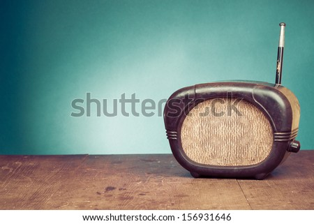 Retro radio on table in front mint green background - stock photo