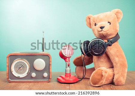 Retro radio, Teddy Bear with headphones, old red microphone front mint green background - stock photo