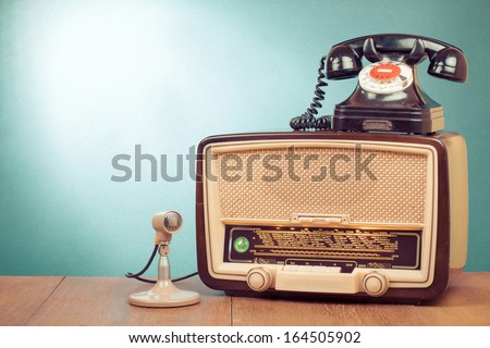 Retro radio with green light, microphone and telephone on wooden table - stock photo