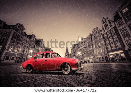 Retro red car on cobblestone historic old town in rain. The market square at night. Wroclaw, Poland. - stock photo