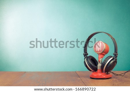 Retro red microphone and headphones on table front mint green background - stock photo