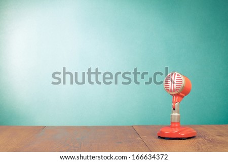 Retro red microphone on table front mint green background - stock photo