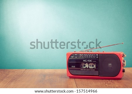 Retro red radio cassette player on table in front mint green background - stock photo