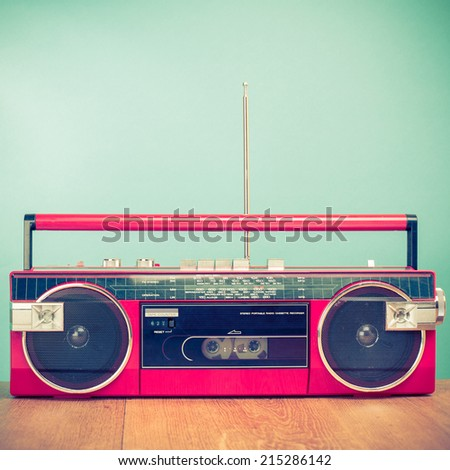 Retro red radio cassette stereo tape recorder front mint green background - stock photo