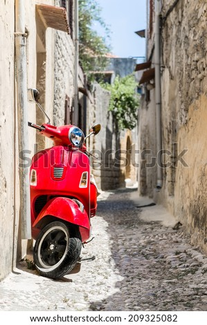 Retro red scooter old town narrow street. Vertical oriented photo. - stock photo