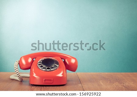 Retro red telephone on wood table near aquamarine wall background - stock photo