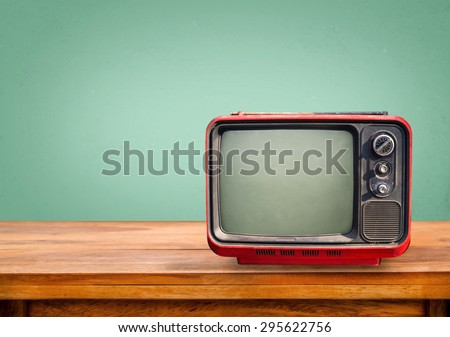 Retro red television on wood table with vintage aquamarine wall background - stock photo