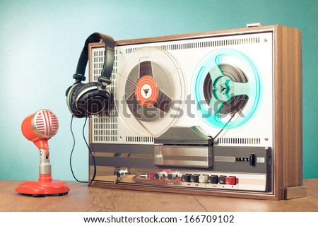Retro reel to reel tape recorder, microphone, headphones in front mint green background - stock photo