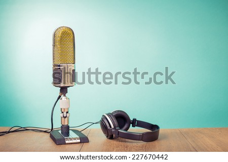 Retro ribbon microphone, headphones on table front mint green background - stock photo