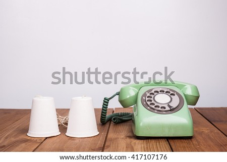 Retro rotary telephone and paper cup phone on wood table - stock photo
