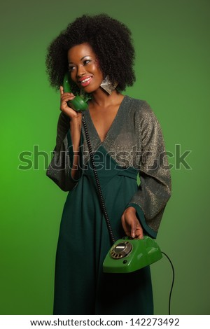 Retro 70s afro fashion woman with green dress. Calling with green phone. Green wall.