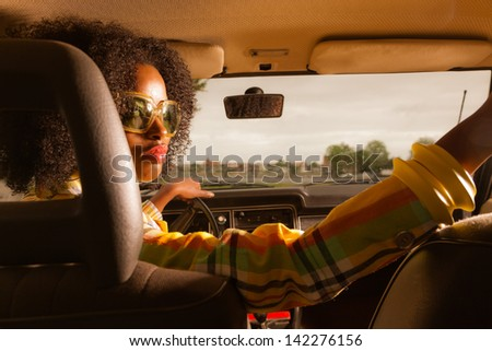 Retro 70s afro fashion woman with sunglasses driving in brown seventies car.
