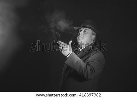 Retro 1930s gangster smoking cigar. Classic black and white portrait. - stock photo