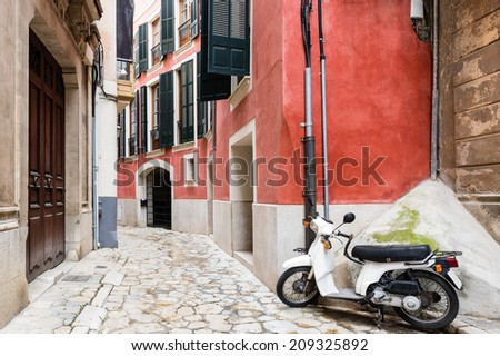 Retro scooter on colorful narrow street in old town - stock photo