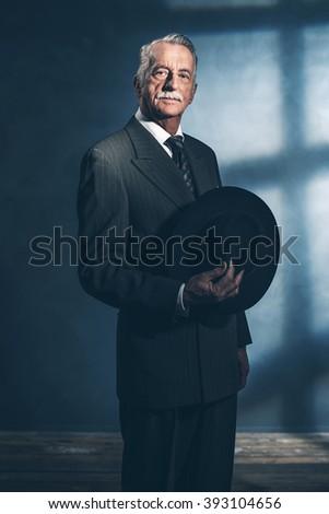 Retro 1940 senior businessman holding hat standing in room. - stock photo