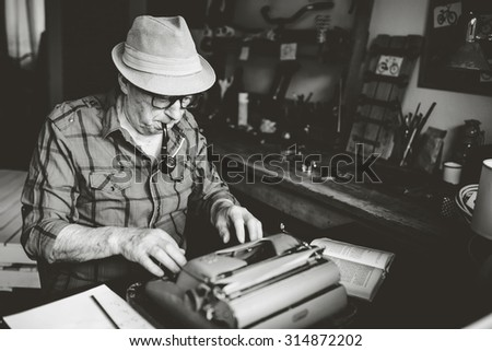 Retro Senior man writer with glasses writing on Typewriter with smoking pipe in his mouth. Black and white photo - stock photo