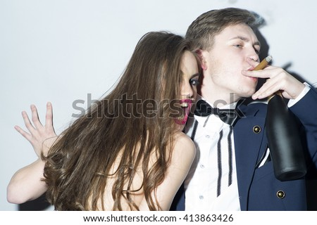 Retro sexy couple of young topless woman with emotional face and man in suit with wine smoking cigar - stock photo