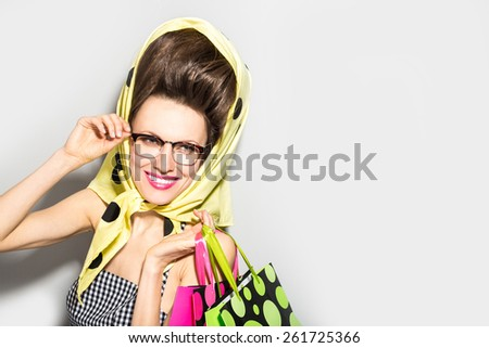 Retro shopping woman looking sideways with excitement over light grey background - stock photo