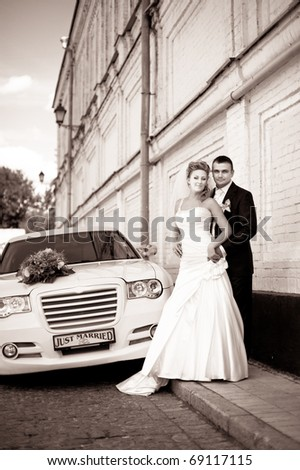 retro shot of bride and groom on the street near the car - stock photo