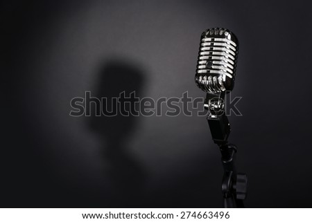 Retro silver microphone on gray background - stock photo