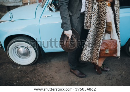 Retro. Sixties. Artwork. The guy in the suit and the girl in a fur coat standing near blue car on its roof piled suitcases - stock photo