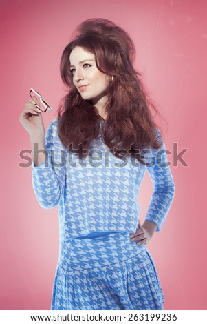 Retro sixties style girl with long hair posing over pink studio background with blue outfit and sunglasses. Bright light and fashion allure. - stock photo
