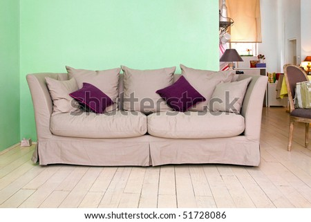 Retro sofa in vintage interior with purple cushions - stock photo