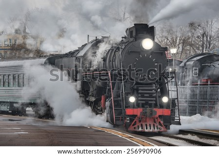 Retro steam train departs from the railway station at evening time. - stock photo