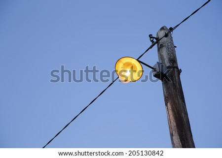 Retro street lamp shining on a wooden lamppost - stock photo