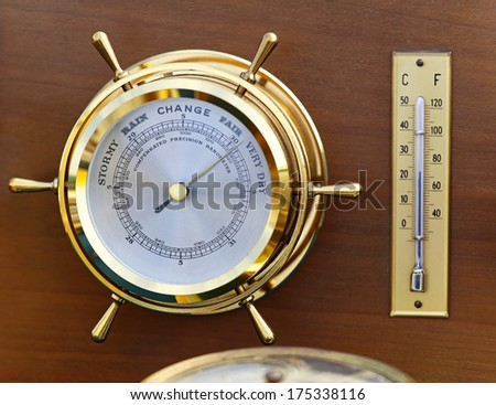 Retro style brass barometer and thermomether weather station - stock photo
