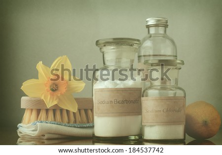Retro style cross processed image of natural cleaning products, including sodium bicarbonate, salt, white vinegar and lemon, folded cloth, bristle brush and a daffodil to suggest Spring cleaning. - stock photo
