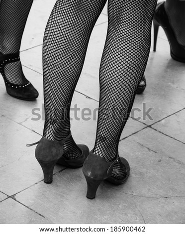 Retro style. Heart tattoo on sexy legs, vintage shoes and fishnet pantyhose. Aged photo. Black and white. - stock photo