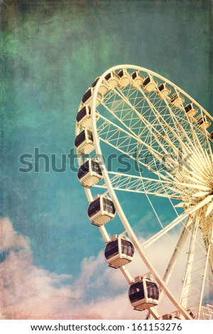Retro style image of a ferris wheel against blue sky. Cross-processed, grunge effect. - stock photo