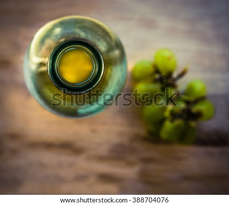 Retro Style Image Of A Rustic Wooden Table With White Wine Bottle And Grapes - stock photo