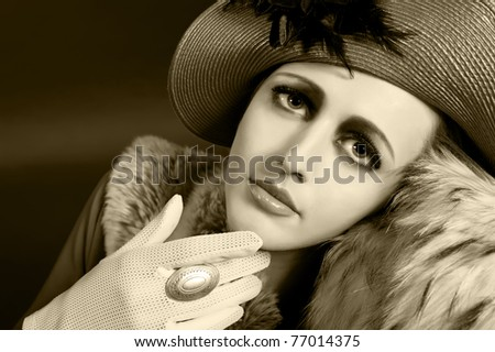 Retro style imitating fashion portrait of a young woman in hat. Clothing and make-up in vintage style. Black&White sepia colored image - stock photo